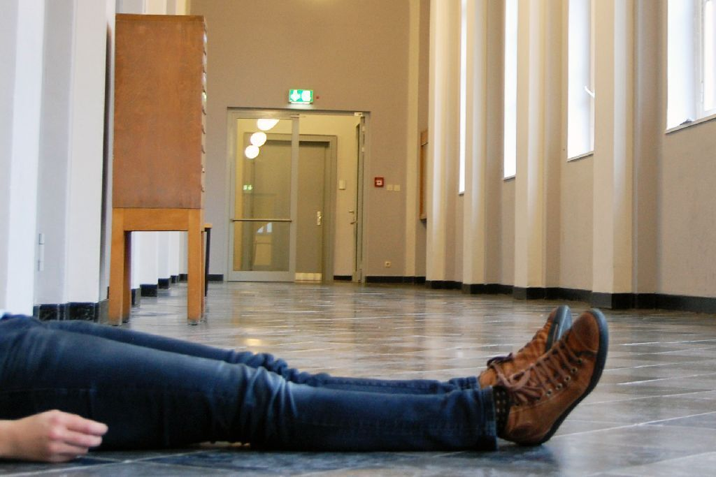 Student sitting on the floor in the hallway
